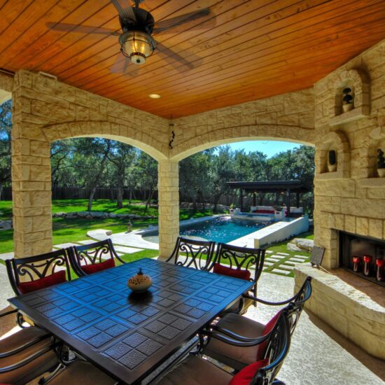 Outdoor living with kitchen and modern pool with beautiful water features.