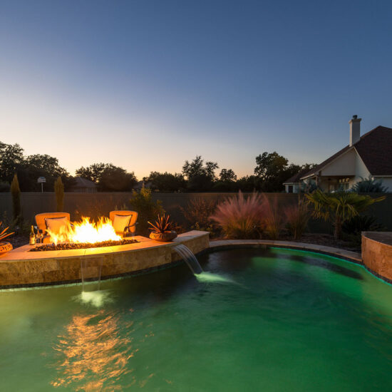Pebble Tec Pool Colors create a green lagoon with a custom fire pit.