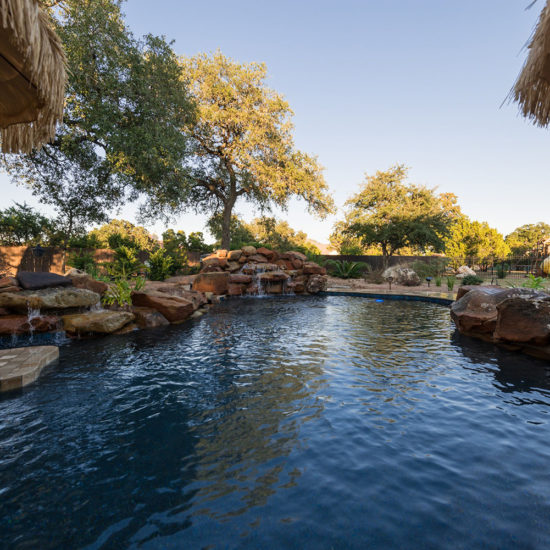 This relaxing backyard retreat and poolscape in San Antonio creates a tropical atmosphere.