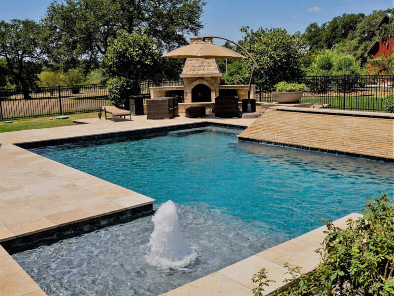 This modern geometric pool features an outdoor fireplace, sheer descent, and stunning water features.