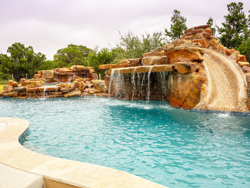 Custom freeform pool features a stunning lateral waterfall grotto and jump rock.