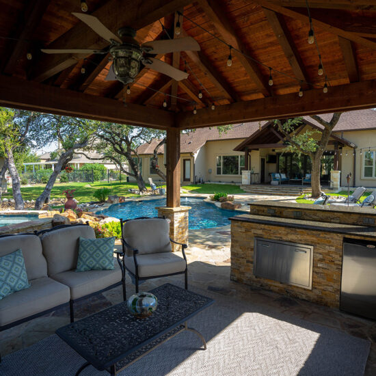 This custom poolscape features a relaxing backyard kitchen and outdoor living space.