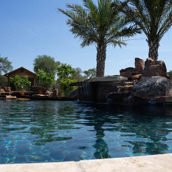 Poolscape with beautiful water features, accent boulders and rock waterfall