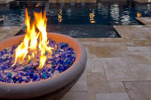 A fire bowl next to a modern pool design