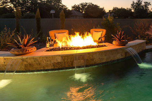 A poolscape with fire pit pool feature
